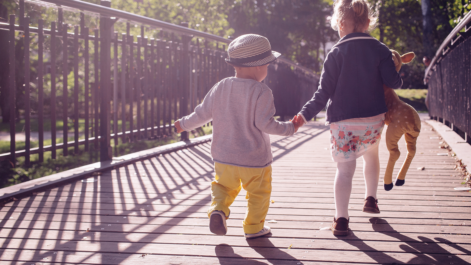 Two small children walking away, over a wooden bridge.