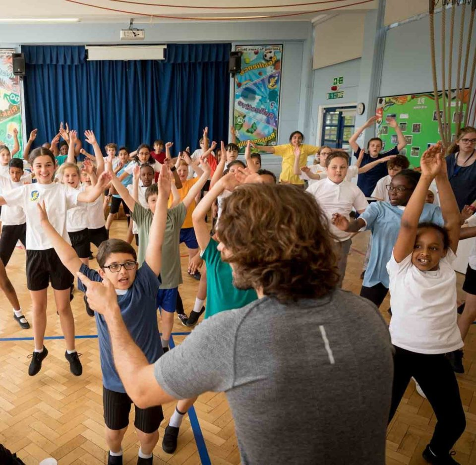 group of children exercising in school hall with Joe Wicks