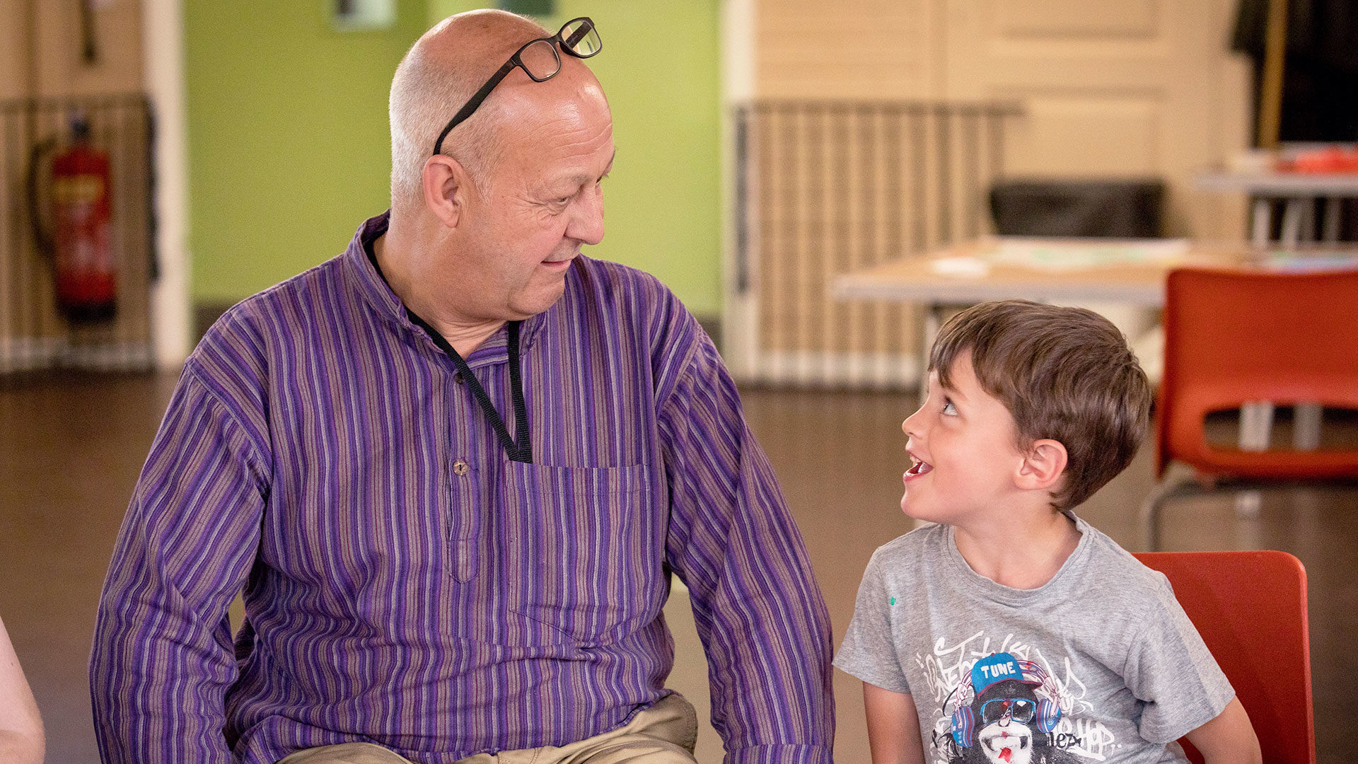 Young boy laughing at an older male volunteer in a group session
