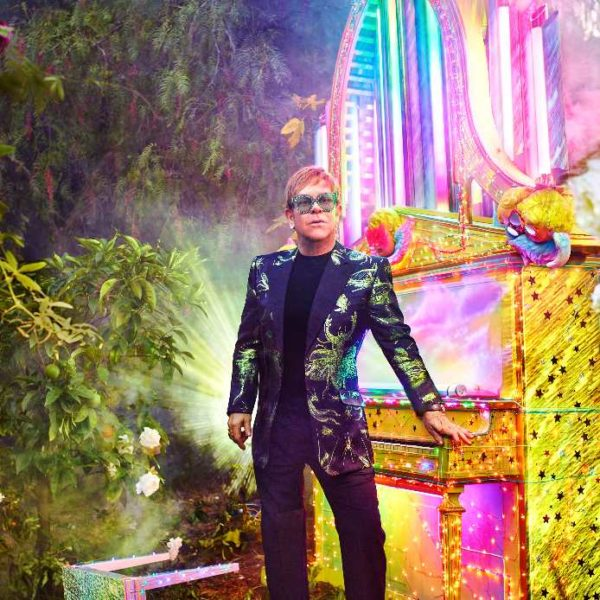 Elton John leaning against a piano surrounded by greenery and coloured lights
