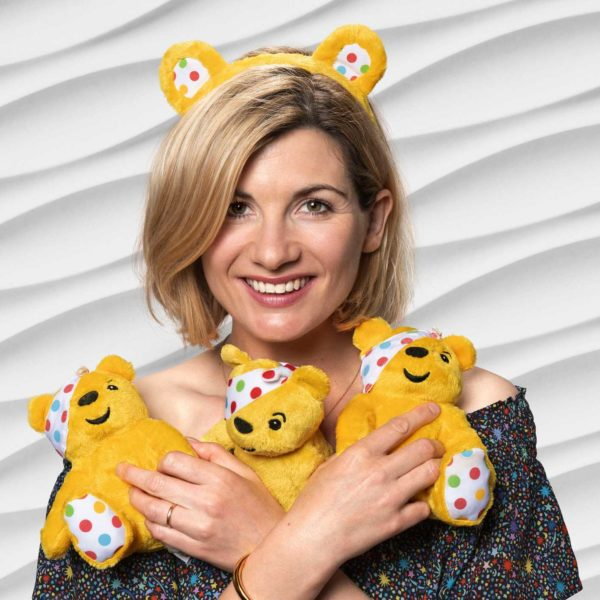 Jodie Whittaker holding three small Pudsey toys