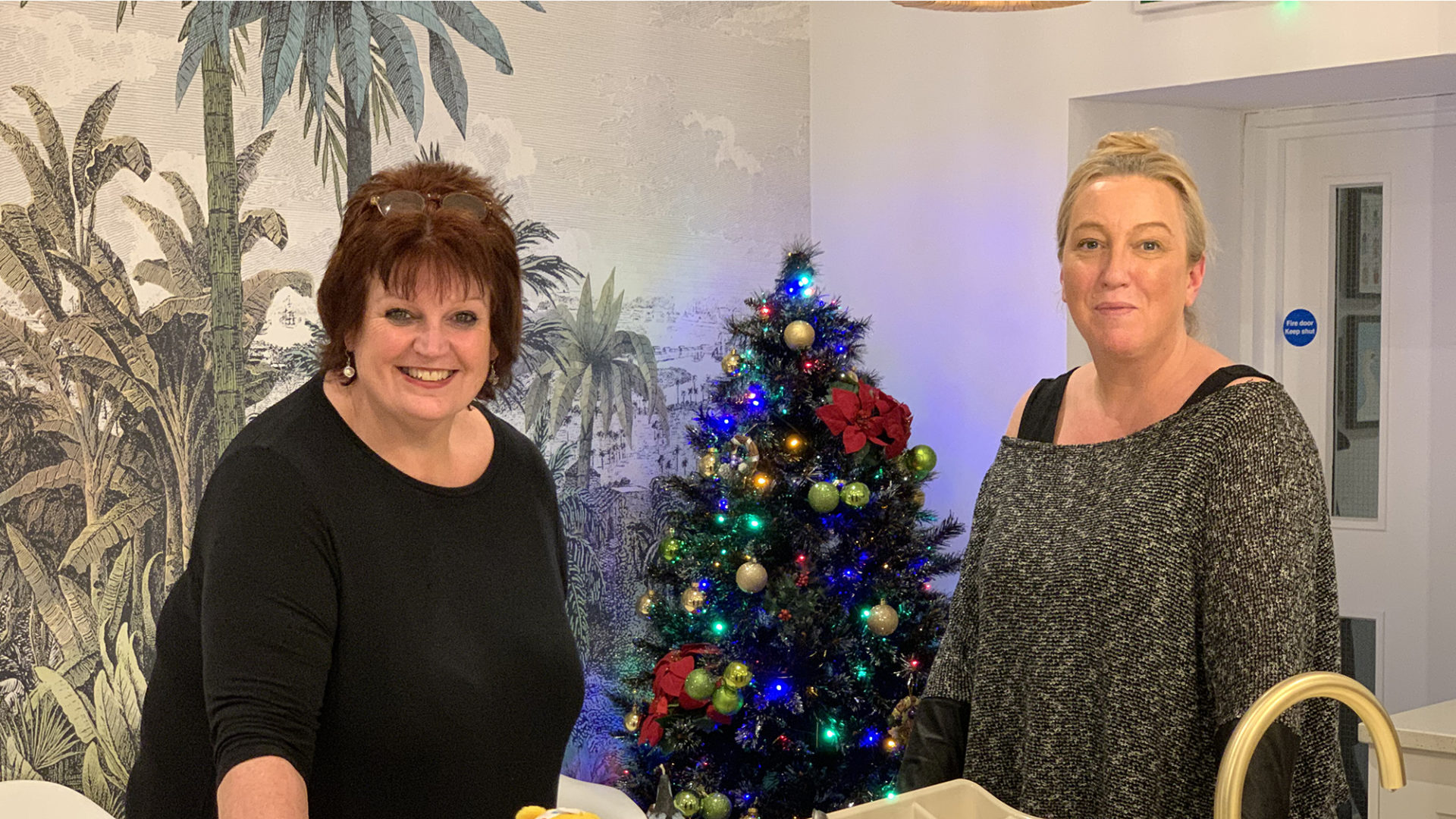 Two project workers from Nightsafe beside the Christmas tree they have put up