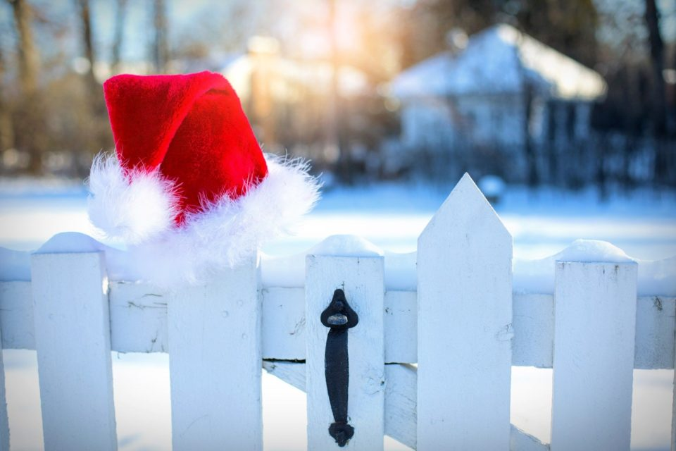 A Santa hat hung on a white gate with a snowy background and a house in the distance