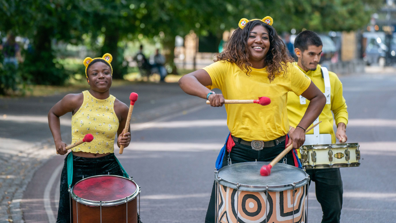fundraisers wearing yellow t-shirts and banging drums