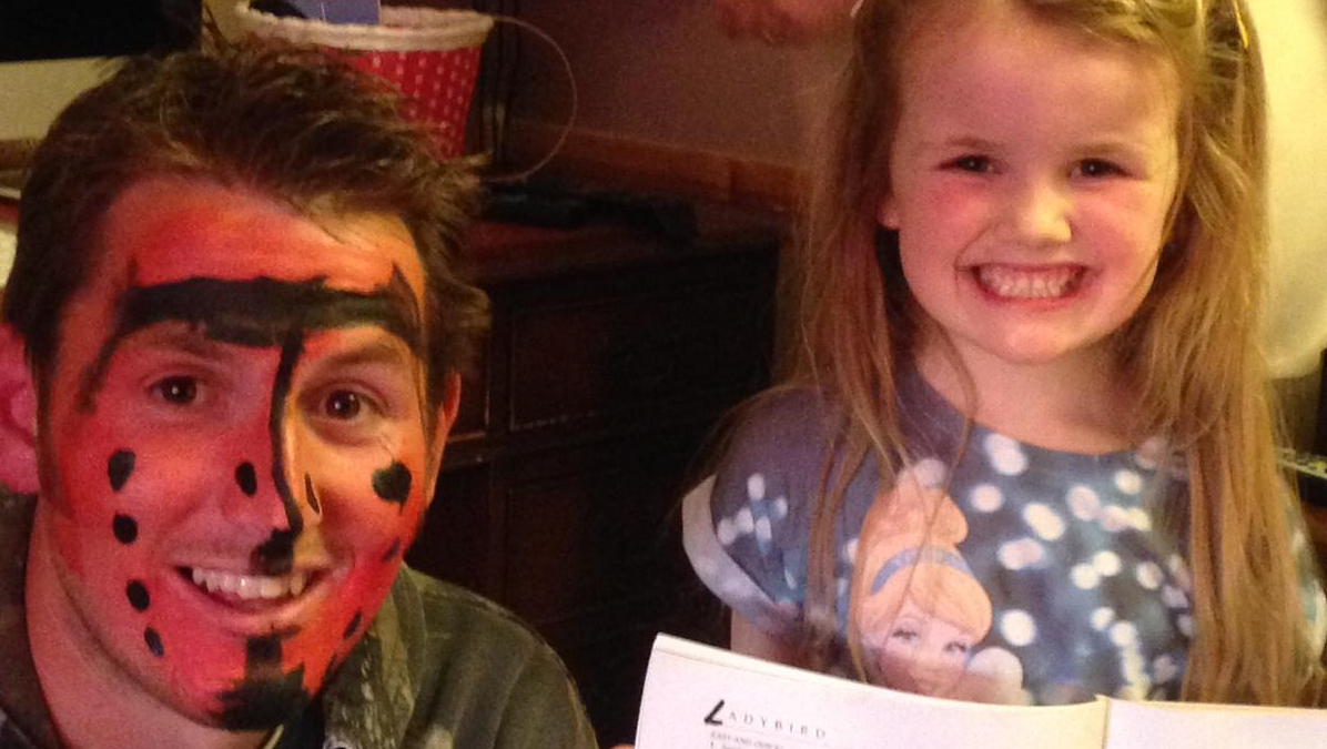 A man wearing face paint next to a child smiling